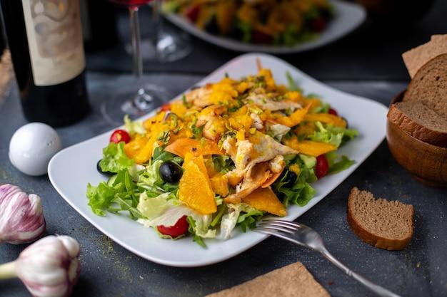 Chips oranje salade met gesneden groenten samen met rode wijn op grijze bureau