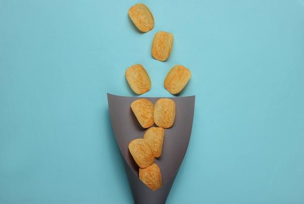 Chips plakjes in papieren zak op blauw