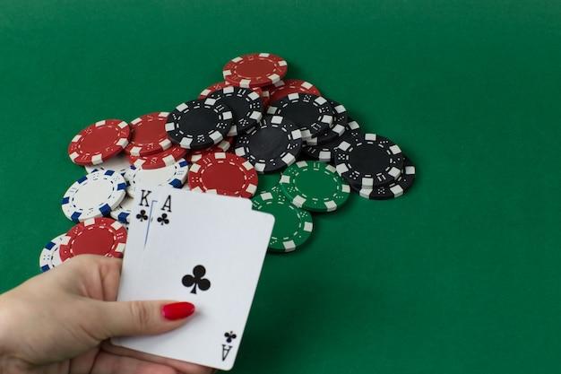 Chips spelen en in vrouwelijke hand twee kaarten: heer en aas