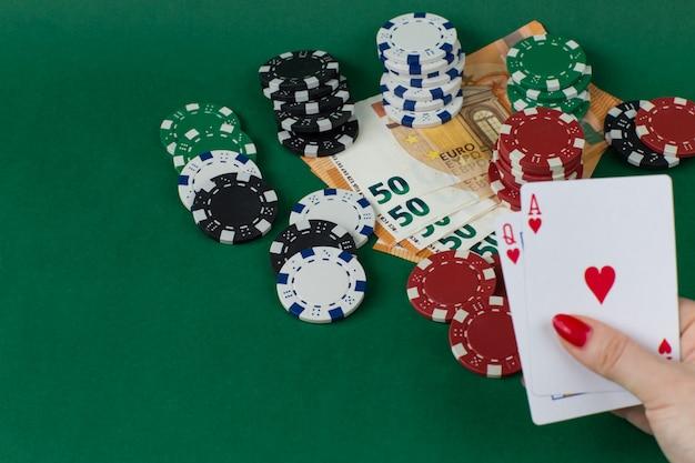 Chips spelen, eurobiljetten en in vrouwelijke hand twee kaarten: vrouw en aas