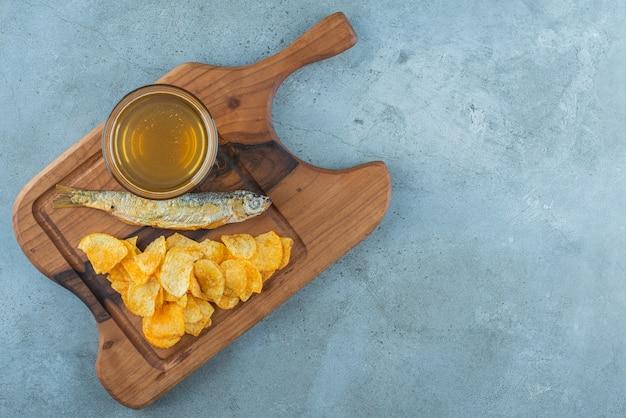 Chips, vis en glas bier aan boord op marmer.