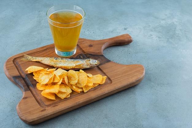 Chips, vis en glas bier op een bord, op de marmeren achtergrond.