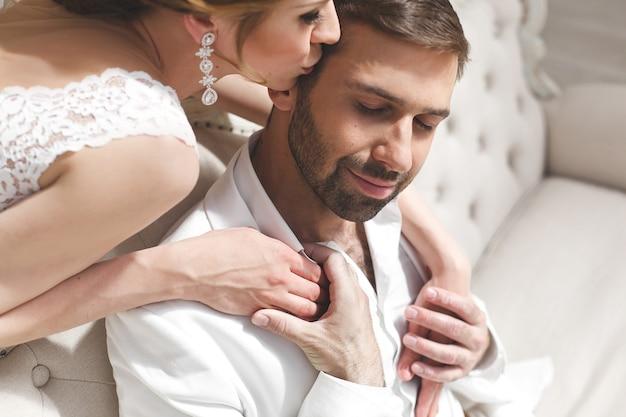 Chique bruidspaar bruidegom en bruid poseren in een witte studio. gelukkig paar lachen. witte jurk. wit pak. jeugd. bruiloft. kroonluchter. bank. de deur.