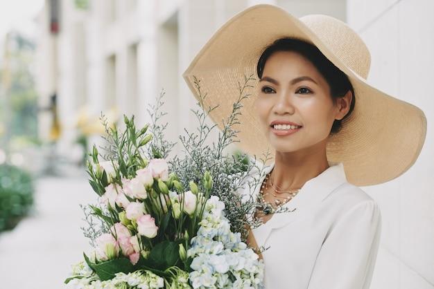Chique rijke aziatische vrouw in grote strohoed poseren in straat met vers bloemboeket