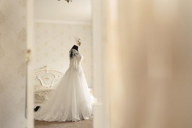 Chique trouwjurk en sluier op een paspop in de vergaderzaal van de bruid. kijk door de deuropening.