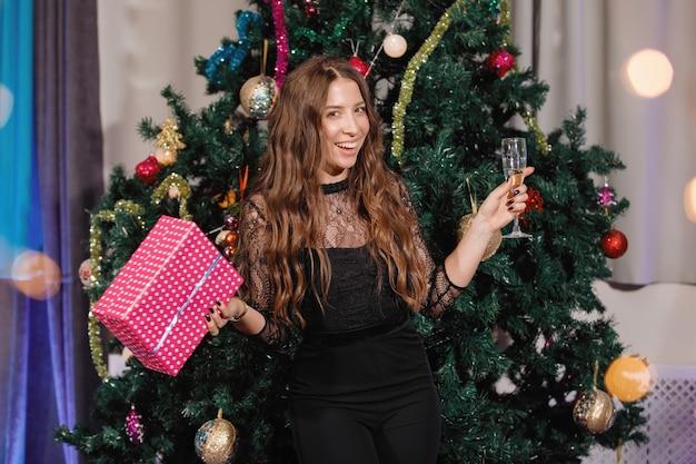 Chique vrouw verheugt zich met een geschenkdoos in de buurt van een kerstboom. een vrouw lacht, glimlacht, poseert. speciale vintage ruis- en graanfilter, wazige lichten.