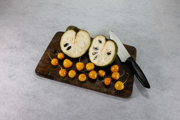 Chirimoya y uchuva aguaymanto uvilla een exotisch peruviaans-latijns amerikaans fruit zit op een bruin houten bord naast een keukenmes