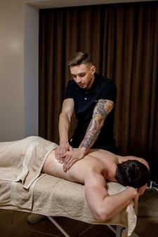 Chiropractie, osteopathie, manuele therapie, acupressuur. therapeut doet genezende behandeling op man.