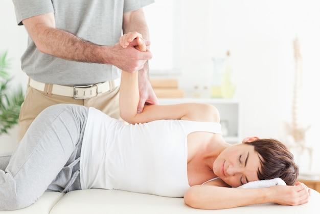 Chiropractor strekt de arm van een klant