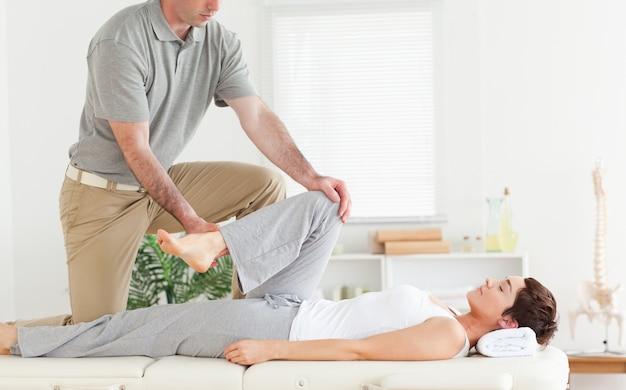 Chiropractor strekt de arm van een vrouw uit