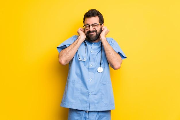 Chirurg arts man die betrekking hebben op oren met handen. gefrustreerde uitdrukking