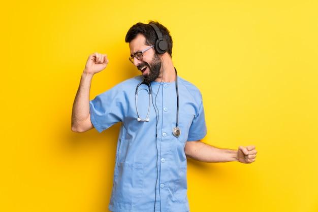 Chirurg arts man luisteren naar muziek met een koptelefoon en dansen