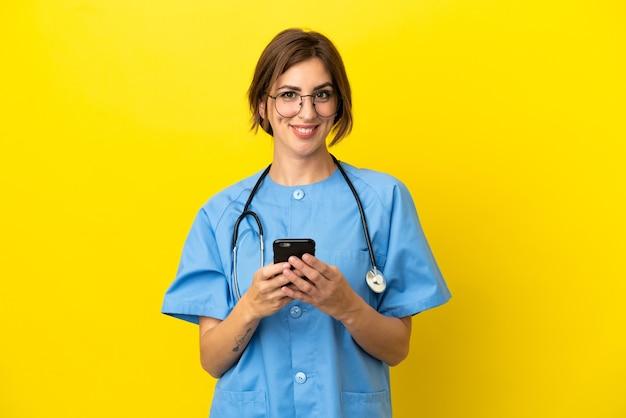 Chirurg arts vrouw geïsoleerd op gele achtergrond die een bericht verzendt met de mobiel