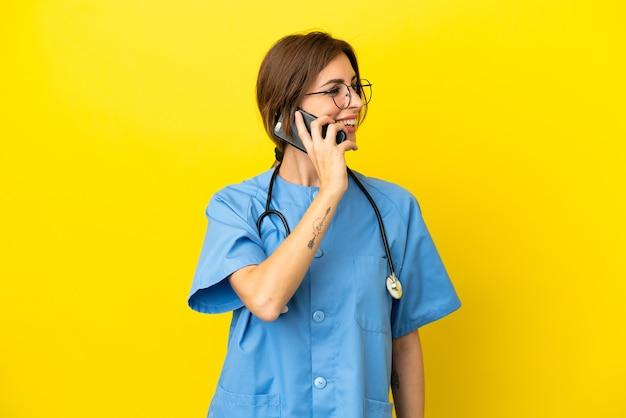 Chirurg arts vrouw geïsoleerd op gele achtergrond die een gesprek met de mobiele telefoon met iemand houdt