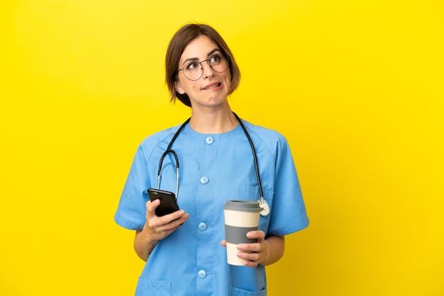 Chirurg arts vrouw geïsoleerd op gele achtergrond met koffie om mee te nemen en een mobiel terwijl ze iets denkt