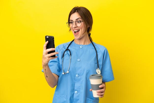 Chirurg arts vrouw geïsoleerd op gele achtergrond met koffie om mee te nemen en een mobiel