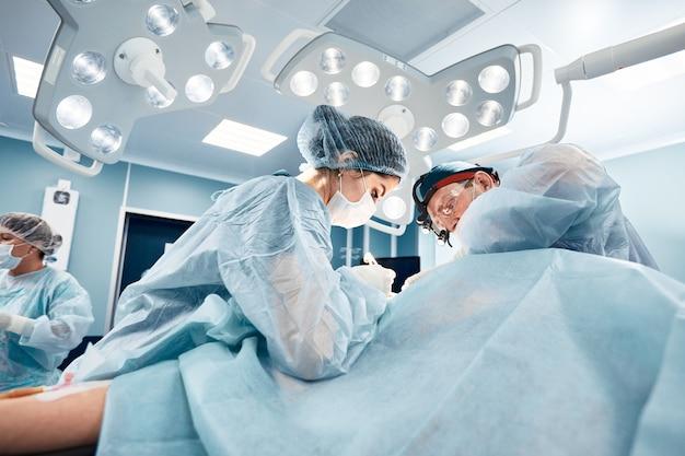 Chirurg-assistent voedt coagulator, plastische chirurgie, professionele artsen, close-up.