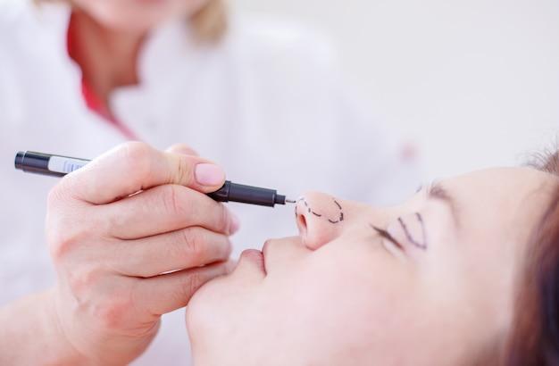 Chirurg corrigeert vrouwelijk gezicht vóór de operatie