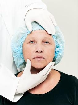 Chirurg doet huidcontrole op middelbare leeftijd vrouw voor plastische chirurgie