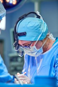 Chirurg en zijn assistent uitvoeren van cosmetische chirurgie in de operatiekamer van het ziekenhuis.