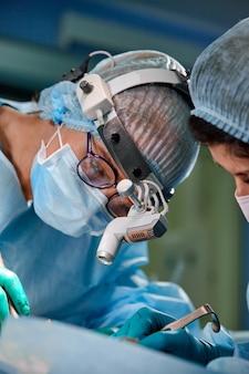 Chirurg en zijn assistent uitvoeren van cosmetische chirurgie op neus in operatiekamer ziekenhuis.