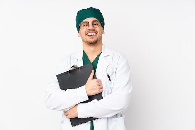 Chirurg in groene uniform op geïsoleerde witte muur