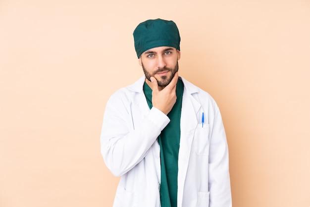 Chirurg man geïsoleerd op beige muur denken een idee