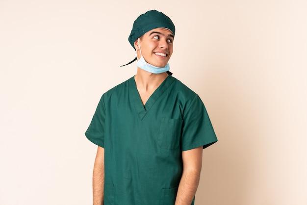 Chirurg man in blauw uniform over muur lachen en opzoeken