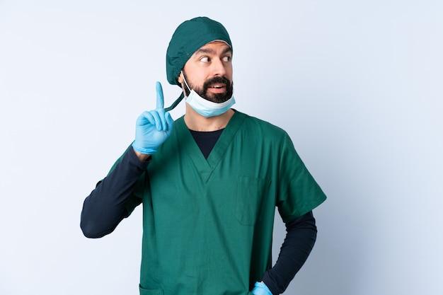 Chirurg man in groen uniform over geïsoleerde muur denken een idee met de vinger omhoog