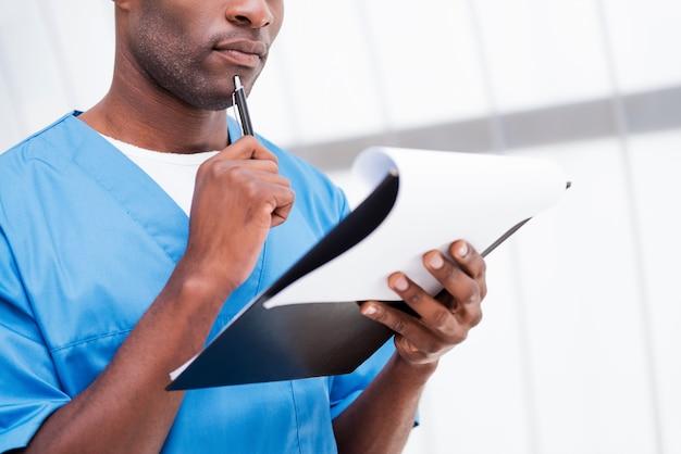 Chirurg met klembord. close-up van een bedachtzame jonge afrikaanse arts in blauw uniform die klembord vasthoudt en zijn kin aanraakt met een pen