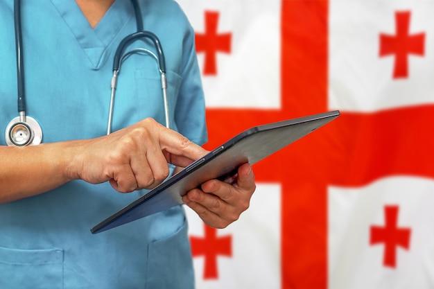 Chirurg of arts met behulp van een digitale tablet op de achtergrond van de vlag van georgië
