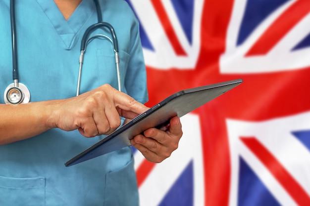 Chirurg of arts met behulp van een digitale tablet op de achtergrond van de vlag van het verenigd koninkrijk