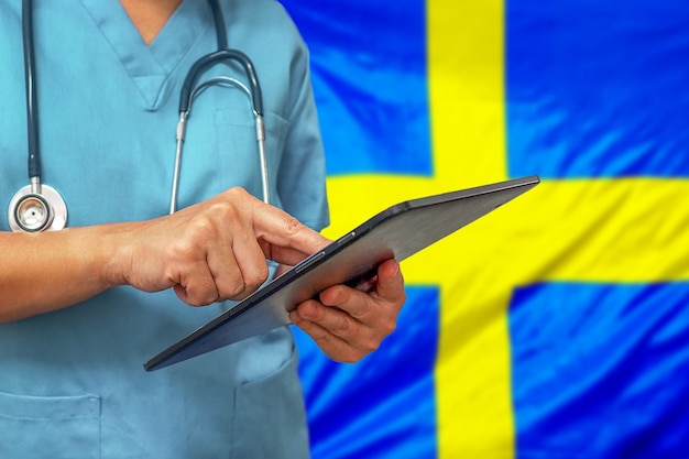 Chirurg of arts met behulp van een digitale tablet op de achtergrond van de vlag van zweden