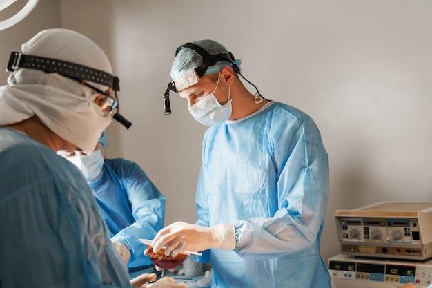 Chirurg opent doos en neemt siliconenimplantaat. borstvergroting plastische operatie in medische kliniek. chirurg plaatst siliconenimplantaat in de borst van de vrouw.