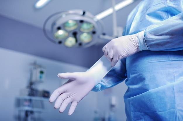 Chirurg rubberen handschoenen aantrekken voor een moeilijke operatie