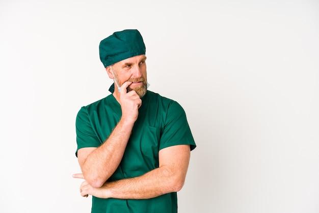Chirurg senior man geïsoleerd op witte achtergrond ontspannen denken over iets kijken naar een kopie ruimte.