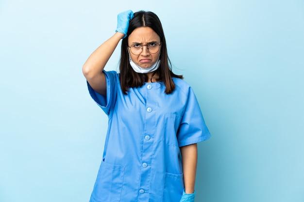 Chirurg vrouw over blauwe muur met een uitdrukking van frustratie en niet begripvol