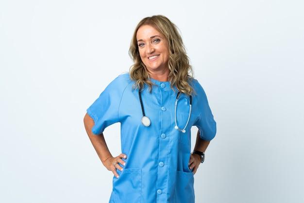 Chirurg vrouw van middelbare leeftijd over geïsoleerde achtergrond poseren met armen op heup en glimlachen