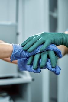 Chirurgen bundelen handen na werk voor reddingspatiënt in operatiekamer in ziekenhuis, noodgeval, chirurgie, medische technologie, ziektebehandeling concept