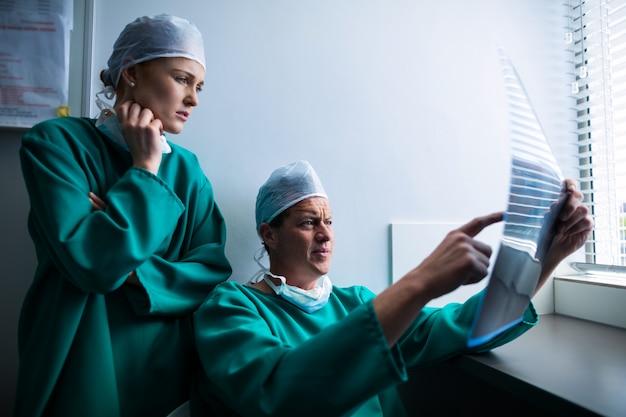 Chirurgen die bij venster zitten en röntgenstraal controleren