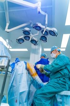 Chirurgen die chirurgische ingrepen uitvoeren in een heldere moderne operatiekamer. operatiezaal. moderne apparatuur in de kliniek. eerste hulp.