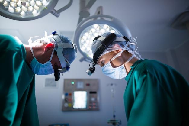 Chirurgen die chirurgische loepen dragen tijdens het uitvoeren van de operatie