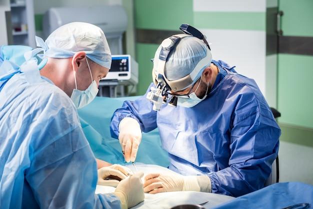 Chirurgen in de operatiekamer die de hand van de patiënt proberen te redden
