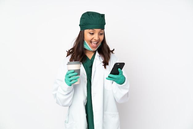 Chirurgenvrouw in groen uniform geïsoleerd op de witte weg te nemen koffie van de muurholding en mobiel