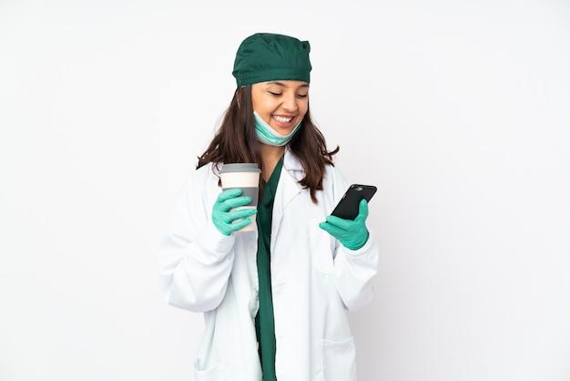 Chirurgenvrouw in groen uniform op de witte weg te halen koffie van de muurholding en mobiel