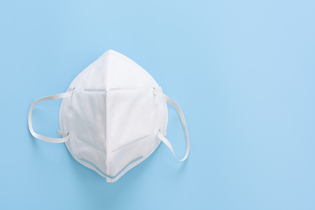 Chirurgisch masker kiem bescherming tegen corona virus op blauwe muur, plat lag