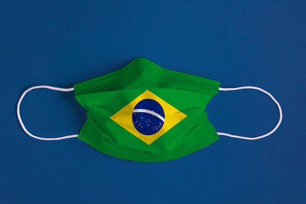 Chirurgisch masker op blauwe achtergrond met braziliaanse vlag