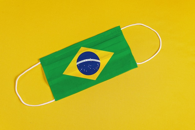 Chirurgisch masker op gele achtergrond met braziliaanse vlag
