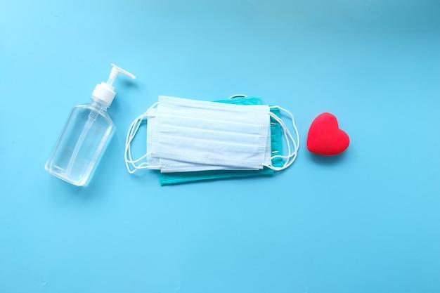 Chirurgische maskers, handdesinfecterend middel met hartvorm op gekleurde achtergrond