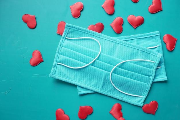 Chirurgische maskers met hartvorm en handdesinfecterend middel op kleur achtergrond